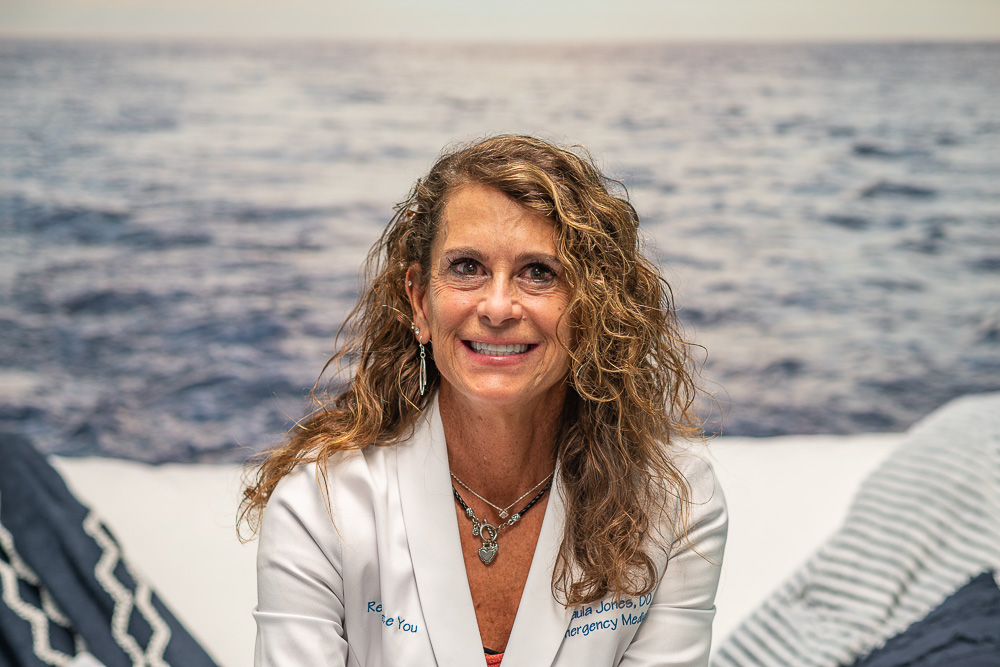 Dr. Paula Jones from Rejuvenate You in a white medical coat against an ocean backdrop (wide frame).
