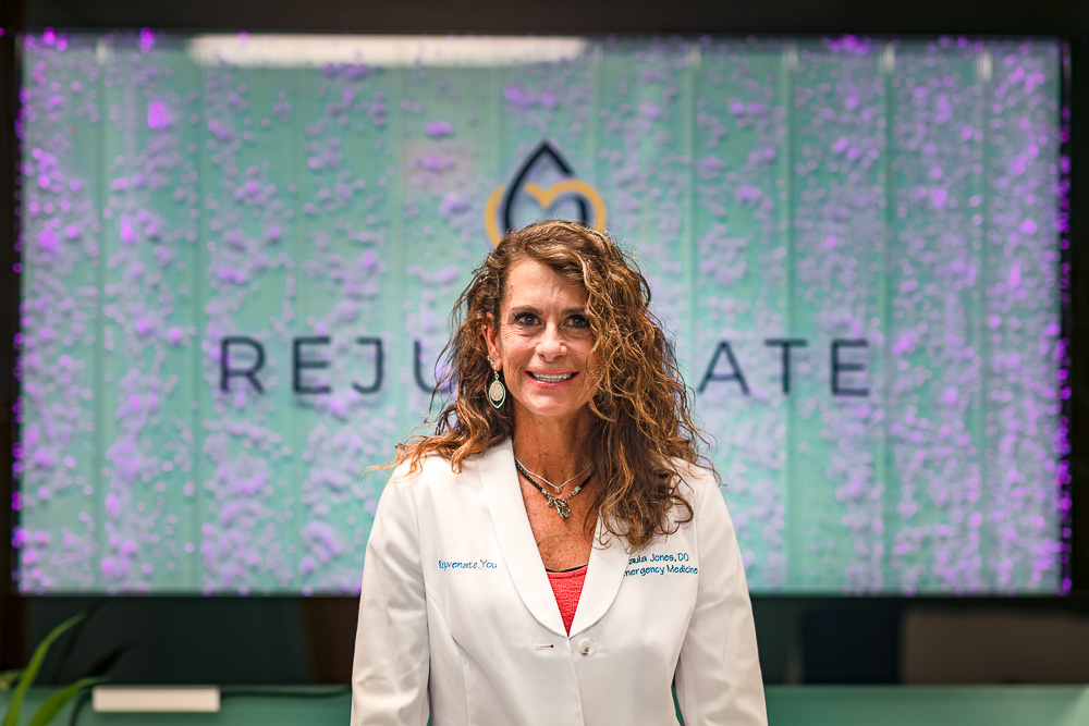 Dr. Paula Jones in front of a Rejuvenate You sign.