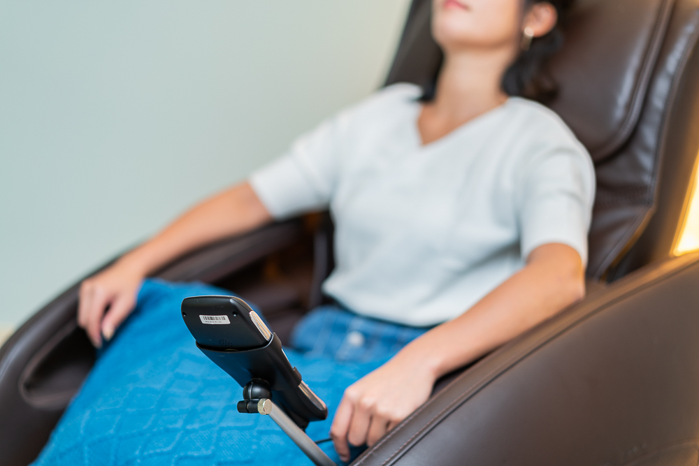 A woman relaxes in a massage chair with a cell phone holder rigged to the left armrest.