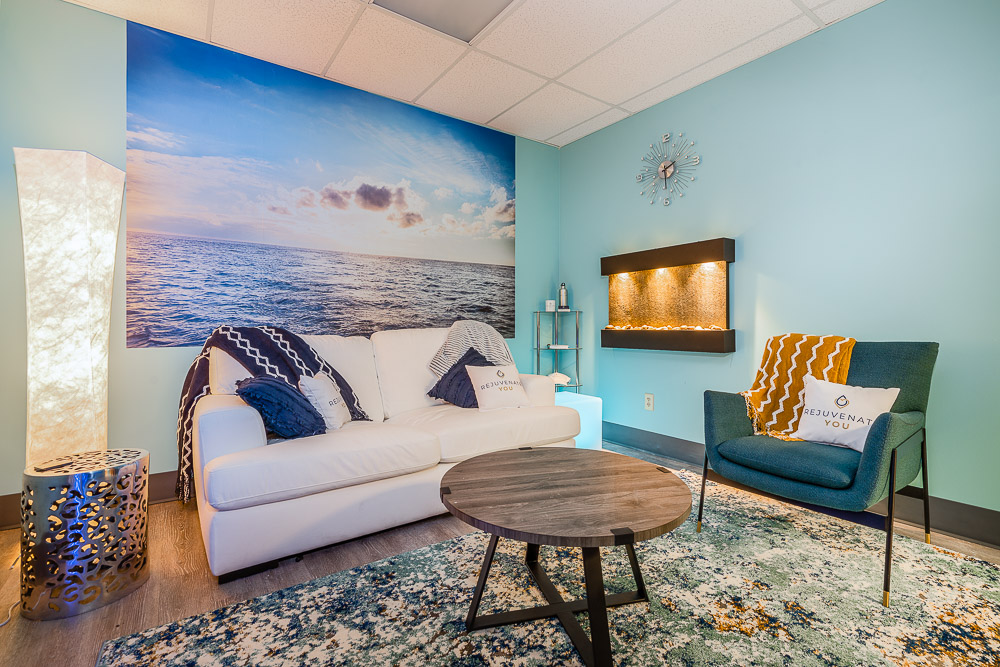 A tropical-looking lobby with a white sofa and a large painting of the ocean.