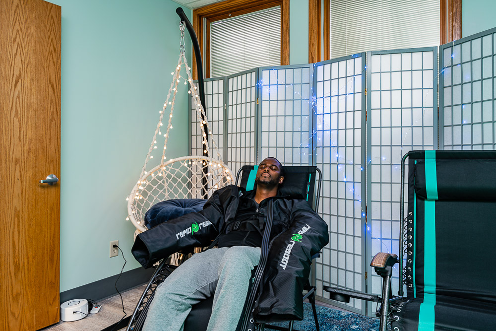Man relzxing with his eyes closed while using NormaTec arm compression units.