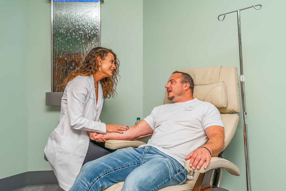 Dr. Paula administering IV therapy to a male patient.
