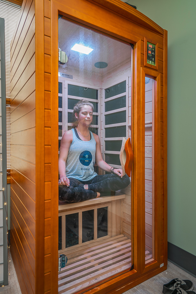 A woman meditating in an infrared sauna as part of an integrated medical approach to her health.