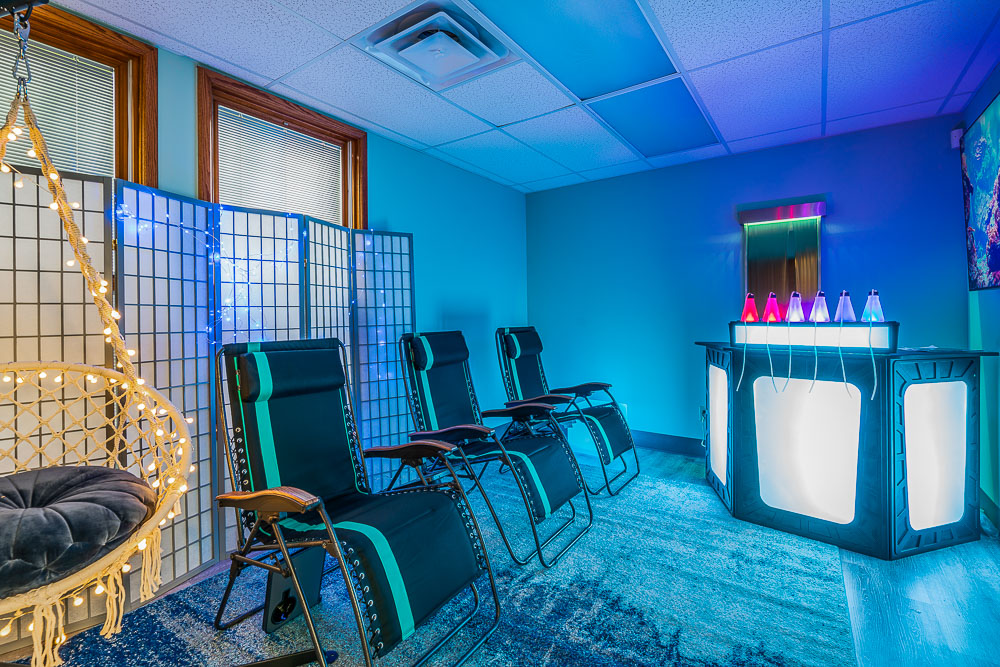 Blue-lit room with oxygen therapy bar and chairs lined up along the wall.