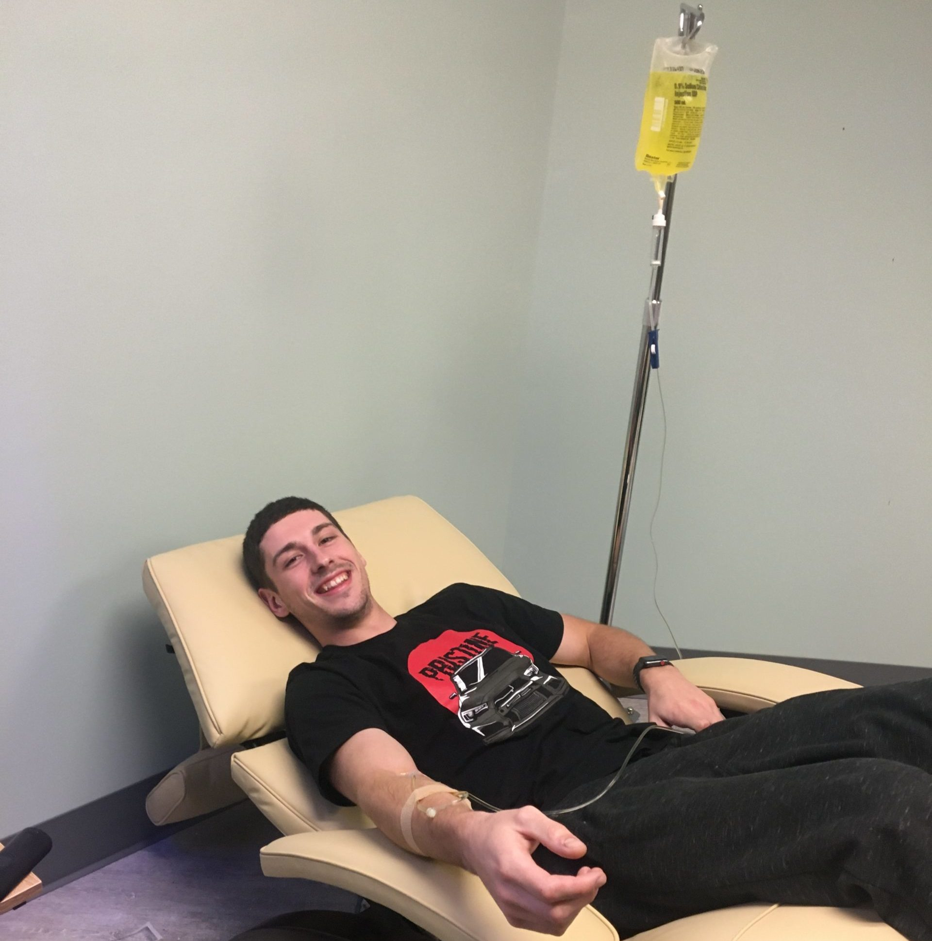 Young man smiling as he an IV bag drips IV hydration nutrients into his right arm.