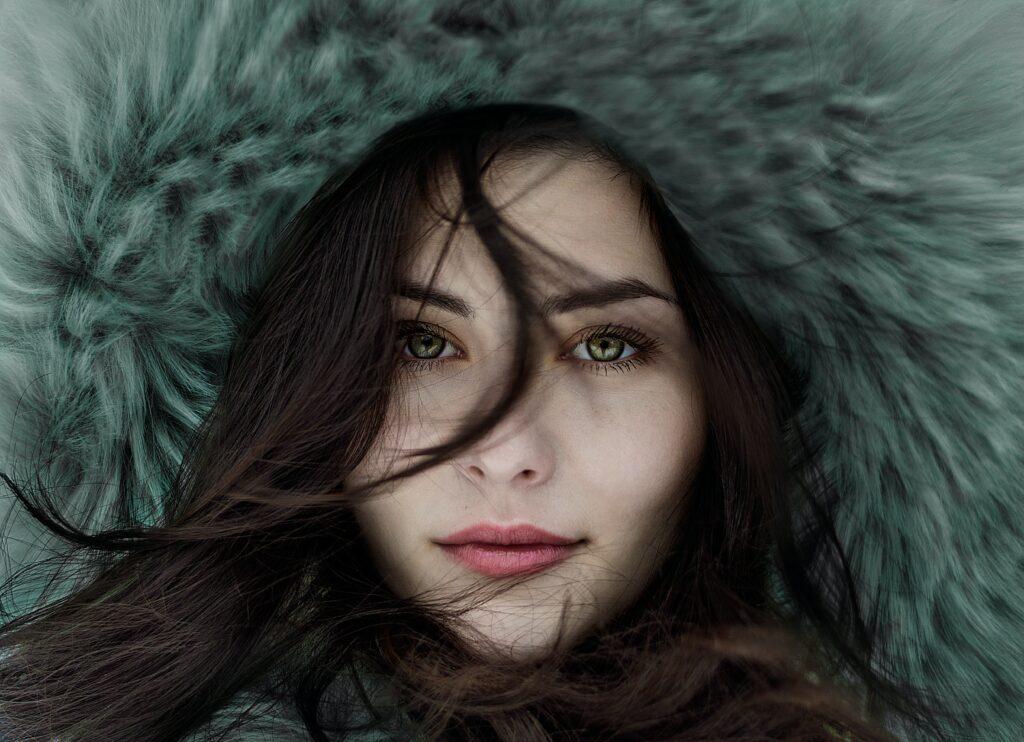 A brunette woman in a fur hood with beautiful skin.