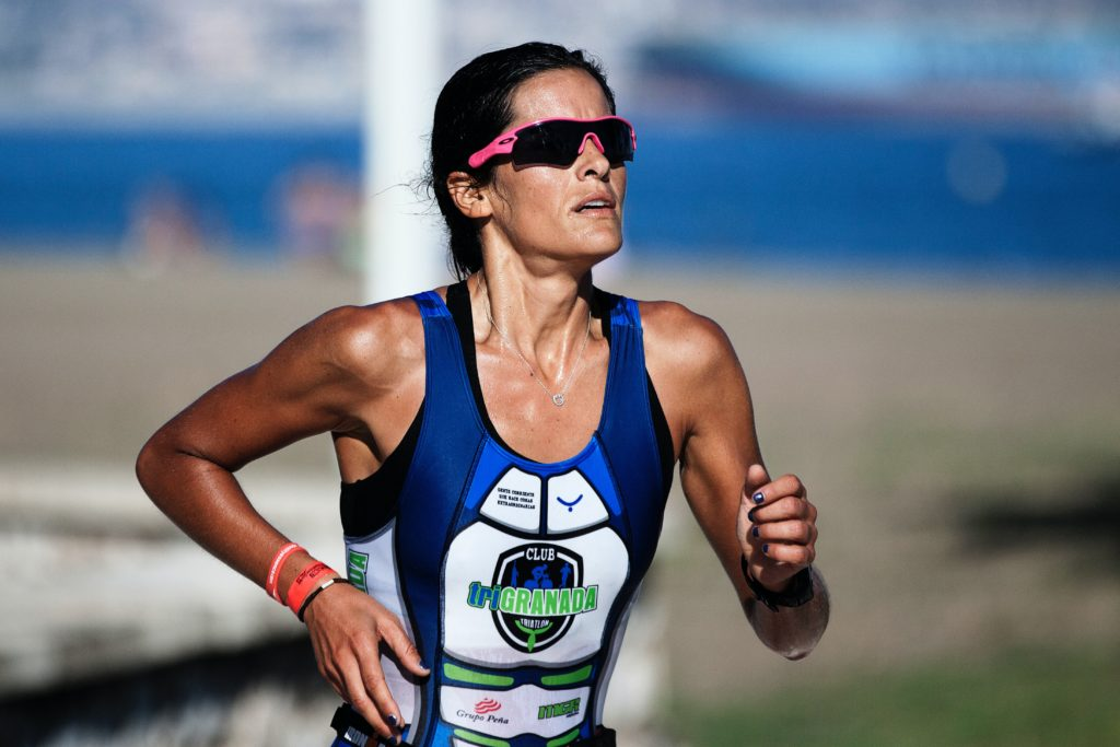 Female long-distance runner for Granada in blue racing tank and pink sunglasses.