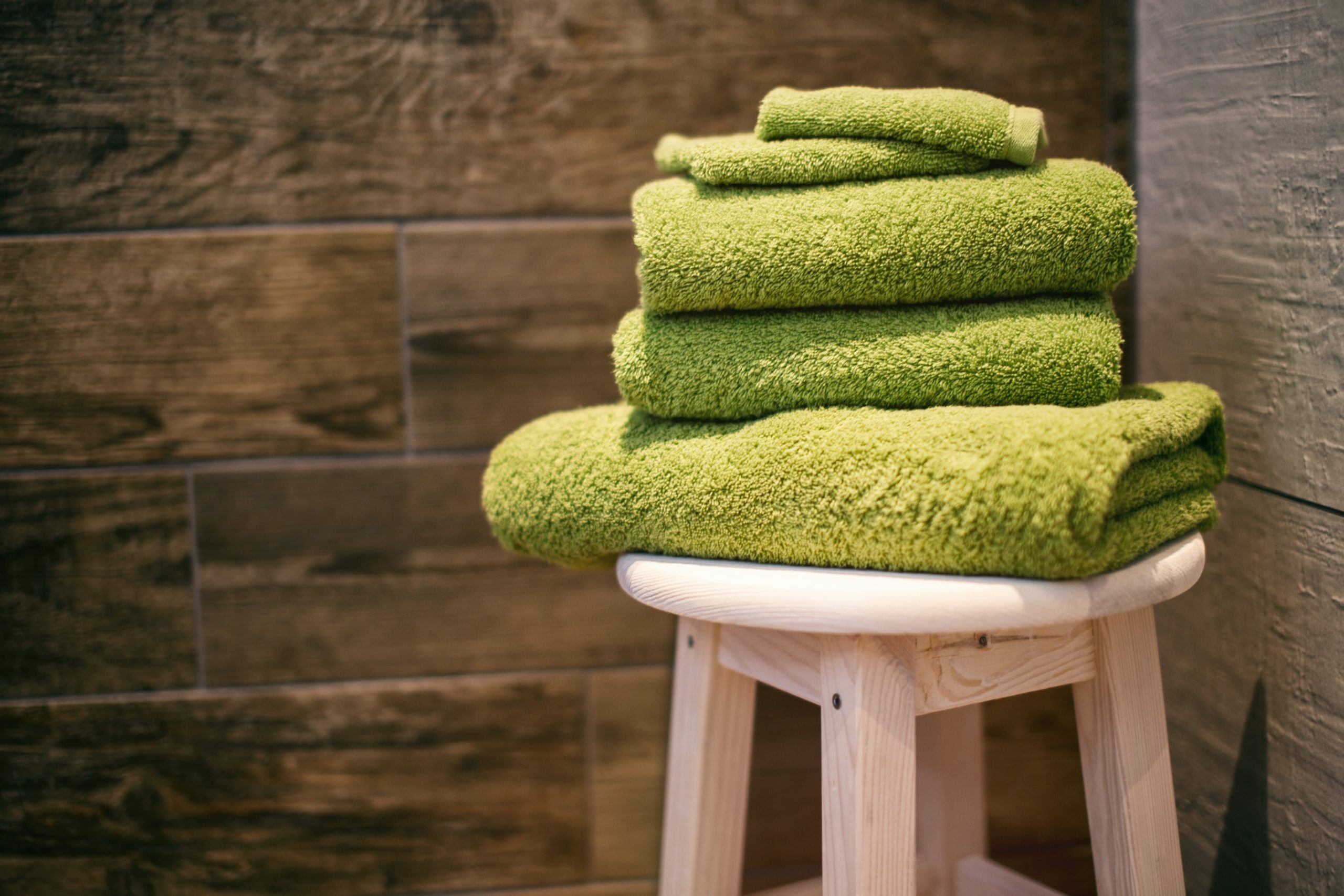 Stack of lime green towels in an infrared sauna.