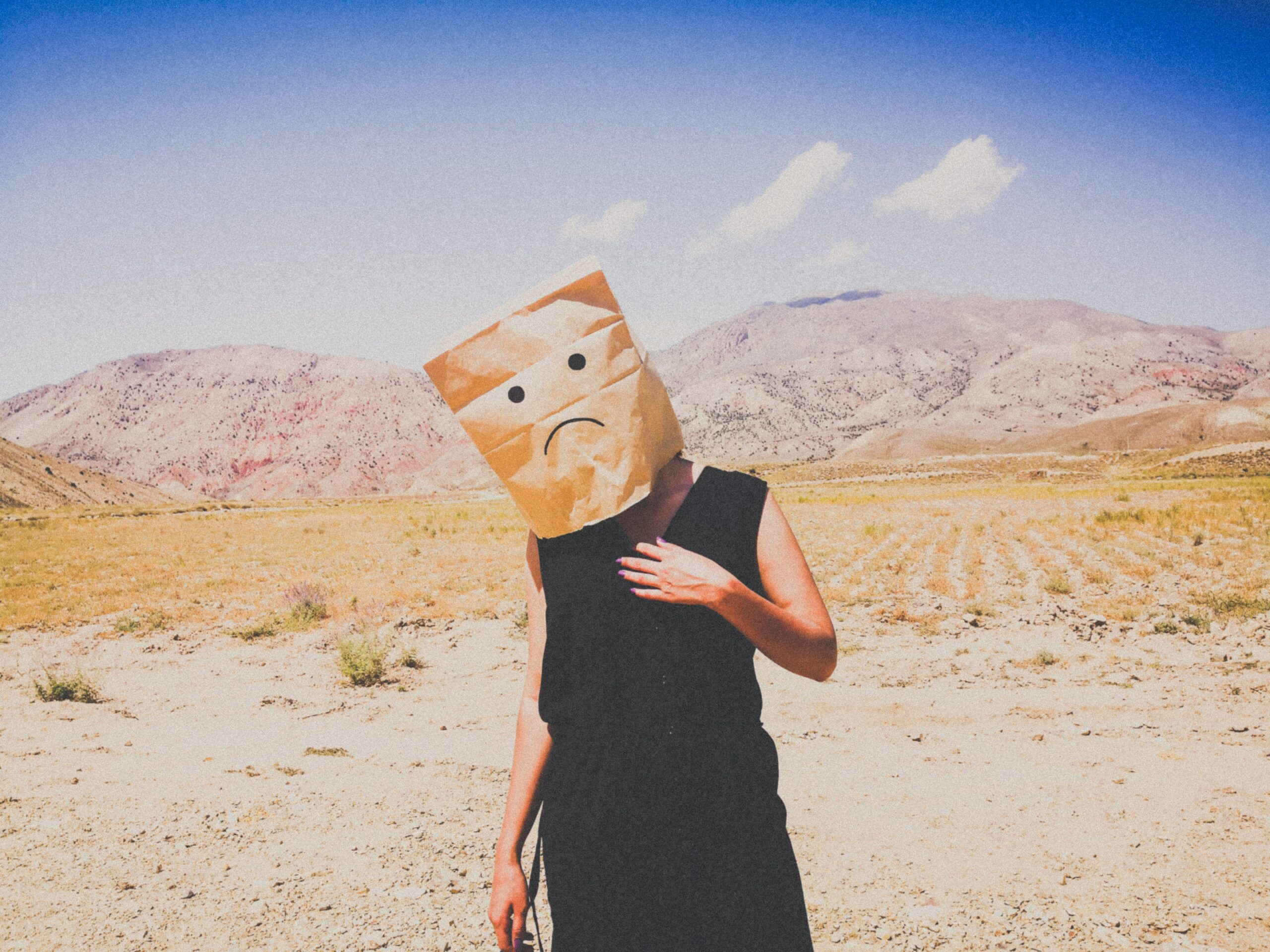 A man with bag and a sad face on his head in the desert.