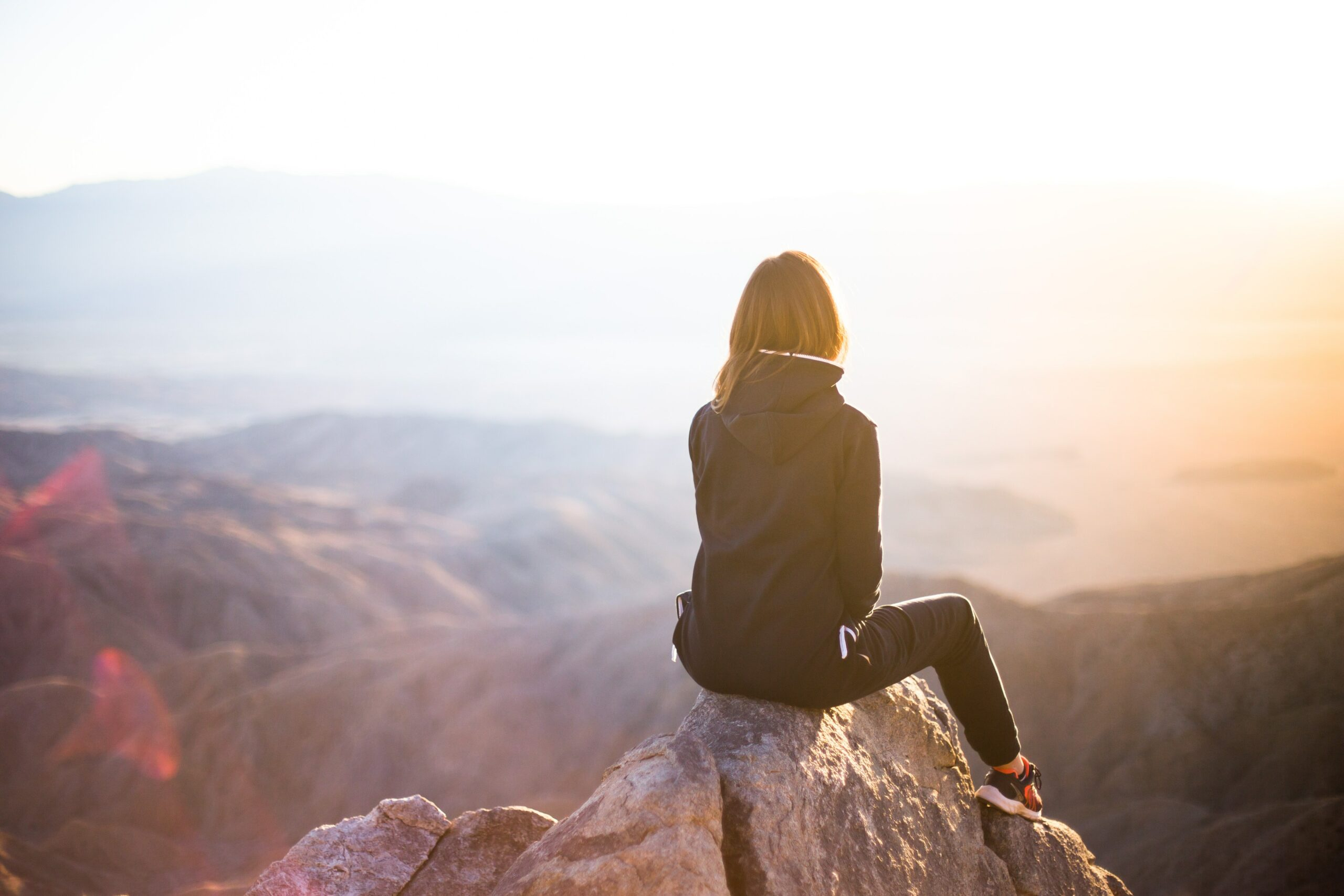 A woman sits on a rock facing out over a valley at sunset.