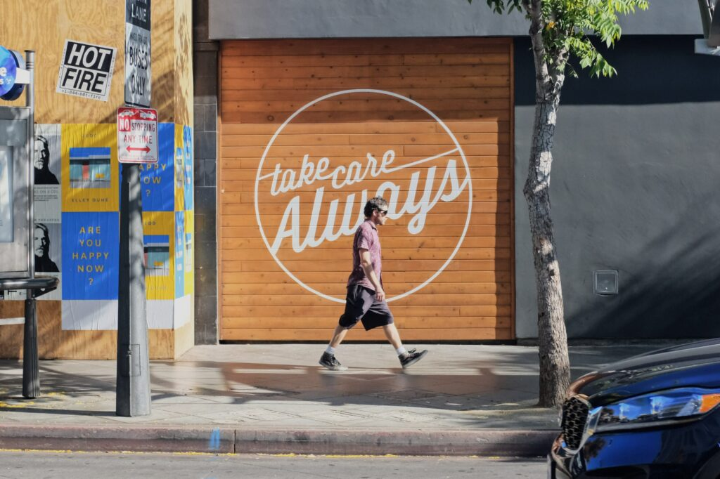 """A fit man in sunglasses walking on a sidewalk in front of a building with the words """"take care Always"""" painted on it in cursive."""