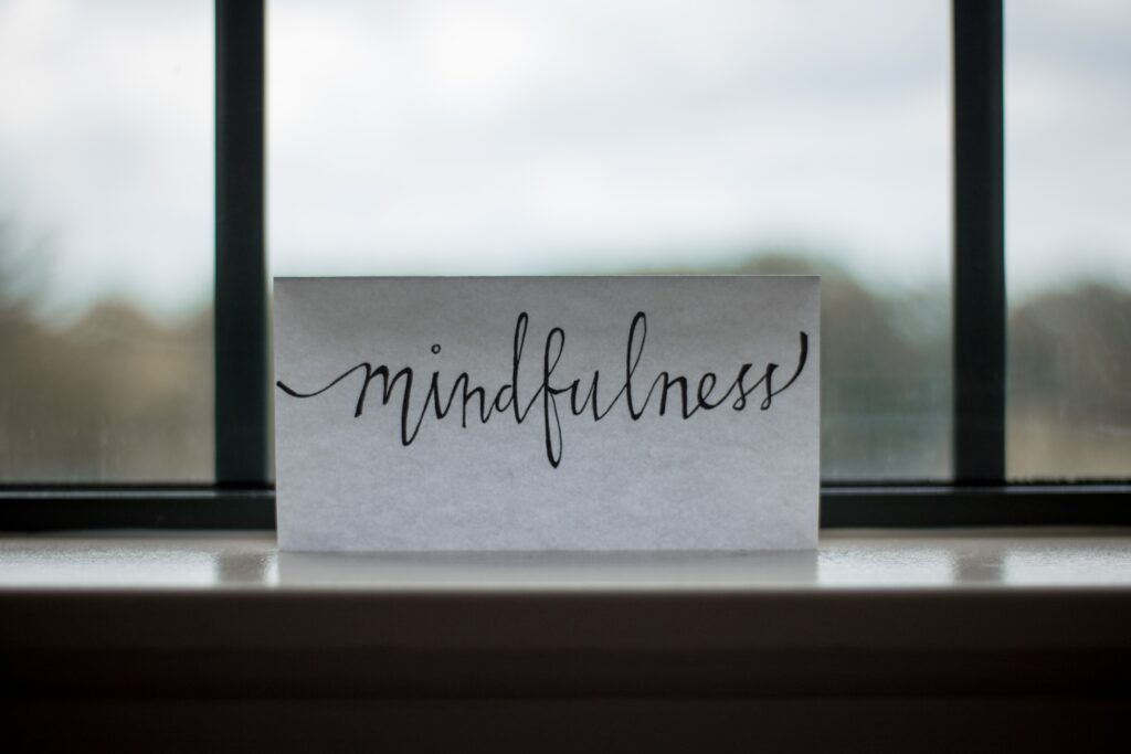 """The word """"mindfulness"""" written in calligraphy on a note in a window."""