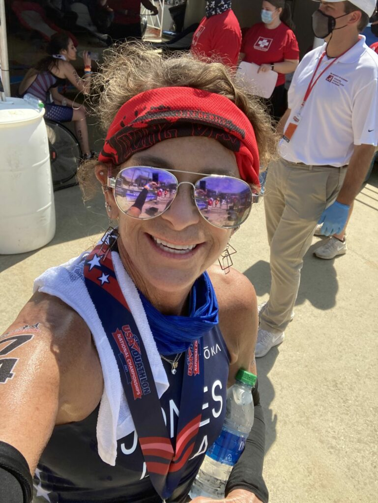 Paula Jones smiling in a pair of purple sunglasses and a tank top after a qualifying duathlon race fueled by vitamin infusion therapy.