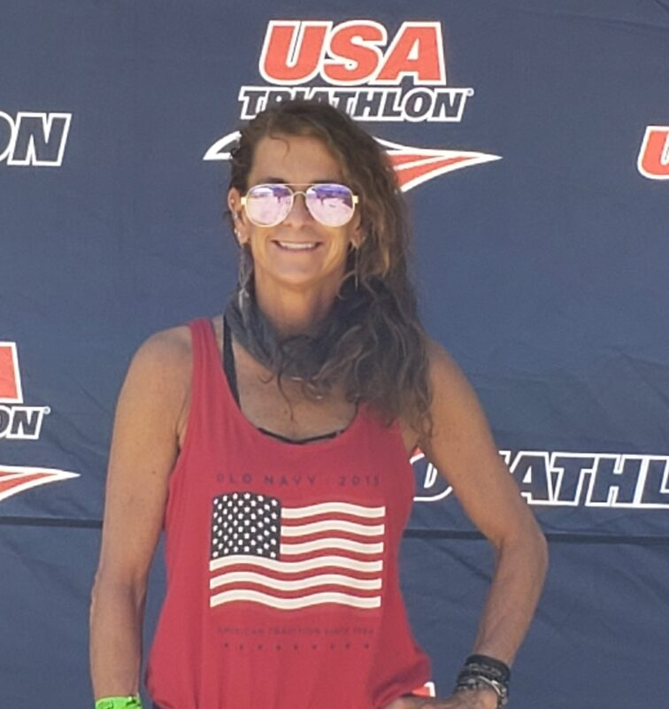 Paula Jones in sunglasses and a red American flag tank top in front of a USA Triathlon banner.