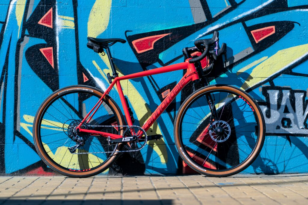 A red race bicycle against an city wall spray painted blue and yellow.