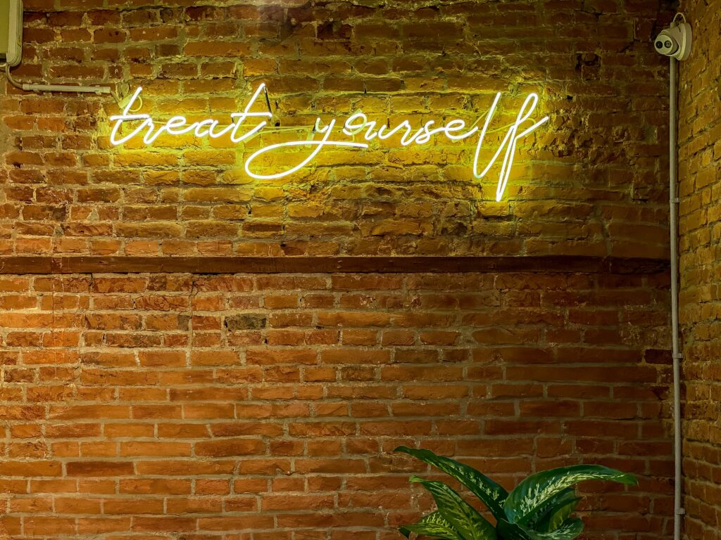 """Neon yellow script that says """"treat yourself"""" on a brick wall."""