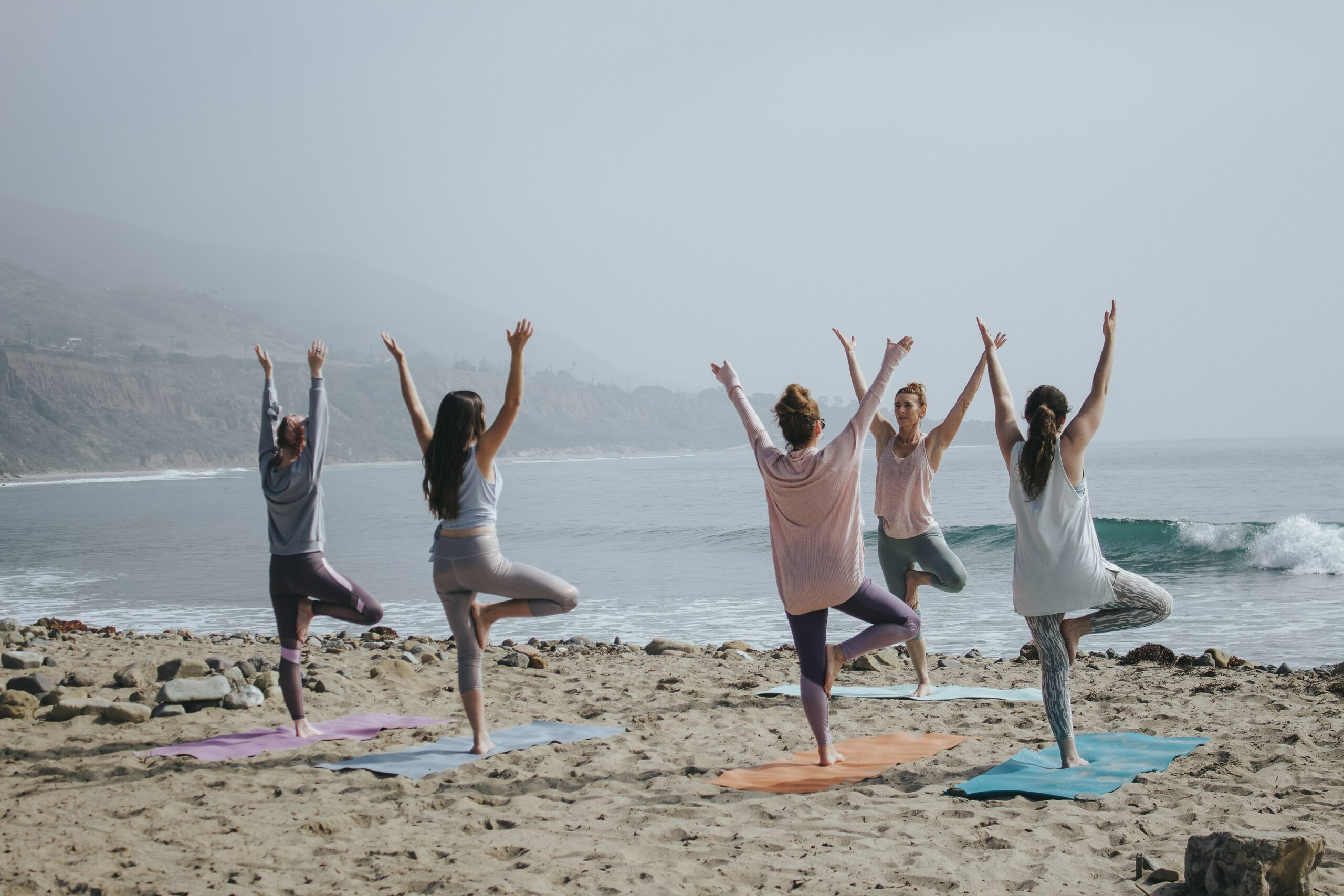 Five women standing on one leg each in yoga poses on a beach.